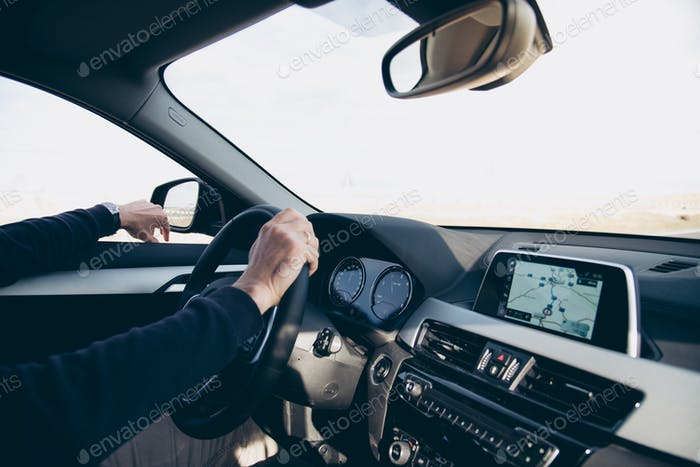 Side view of man driving car with navigation GPS