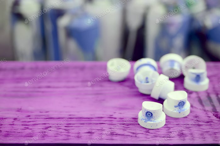 The soiled blue nozzles from the paint sprayer lies on a purple plank on a background of a many dir