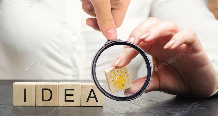 Eine Geschäftsfrau hält einen Holzblock mit einer Glühbirne Idee oder Inspiration