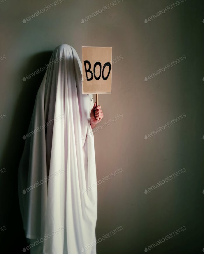 unrecognizable person in Halloween ghost costume holding sign