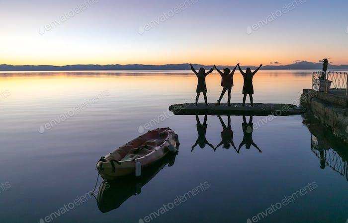 Drei glückliche feierende Frauen stehen begeistert halten ihre Hände hoch