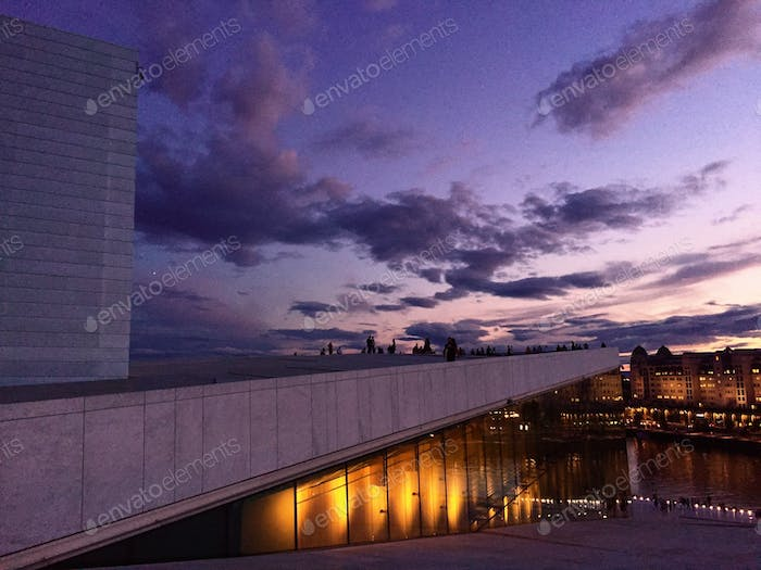 Purple sky over the city of Oslo, modern architecture and city view, incidental people at night