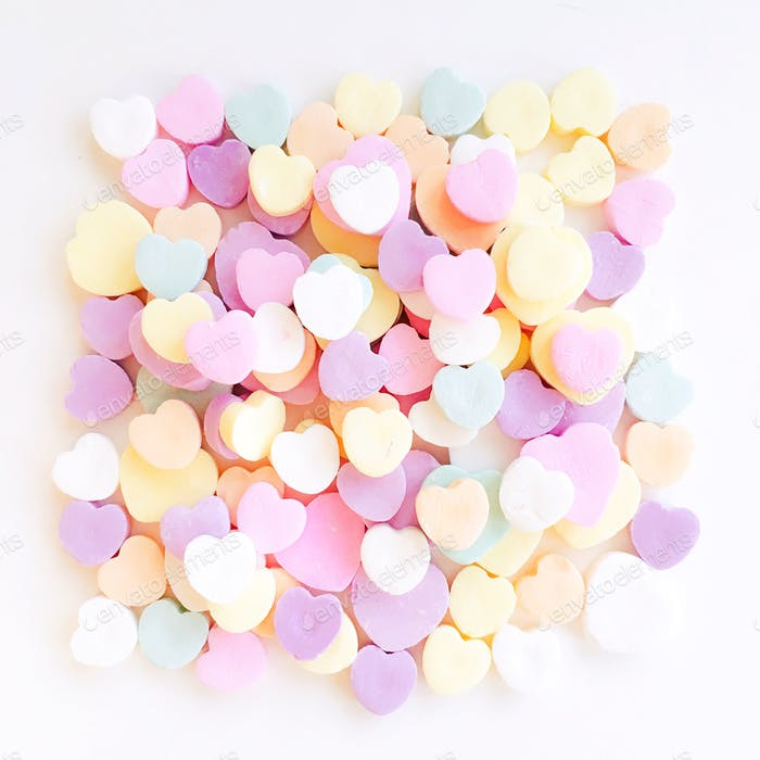 Pile of pastel colored candy hearts on a white background.