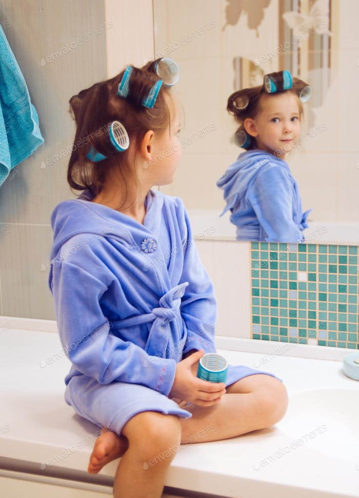 The girl in the bathroom in a blue robe and curlers