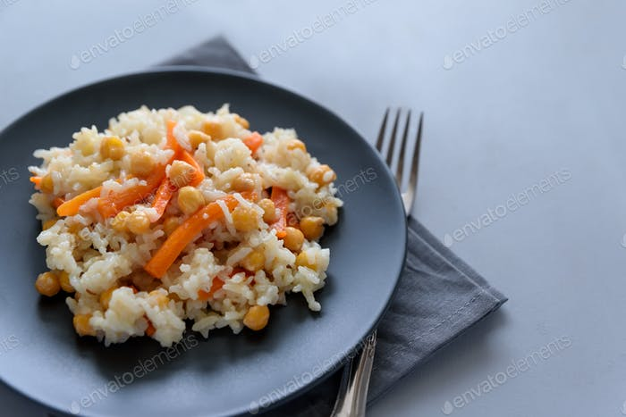 Tasty vegetarian pilaf with rice, carrot and chickpeas on gray wooden background