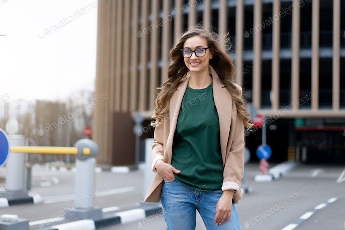 Business woman walking near Parking Garage building Caucasian female business person walking street