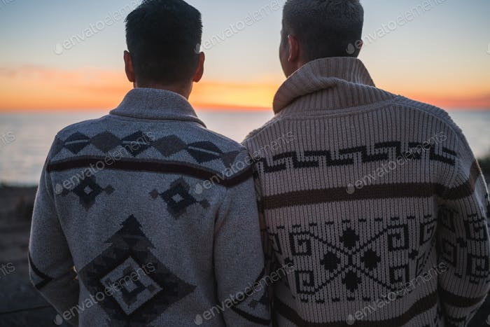Zwei Jungs blicken auf den Sonnenuntergang und reflektieren Leben und Liebe.
