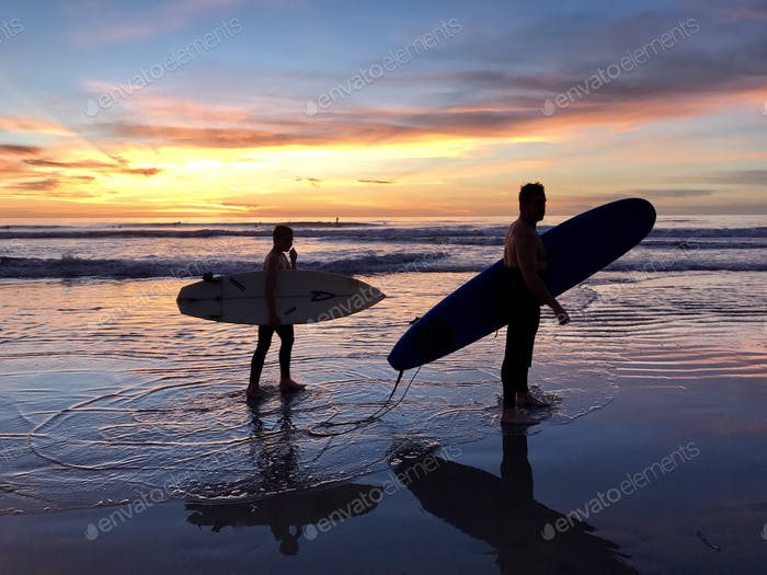 Father and son surfing lessons together at sunset .