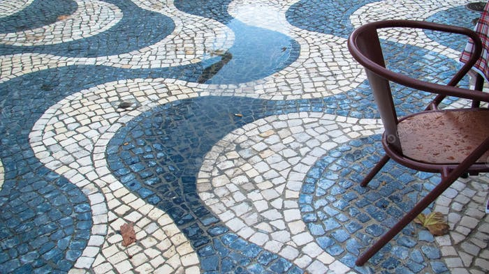 Wet outdoor furniture on a cobbled street. Photo was taken in Cascais, Portugal in November of 2014