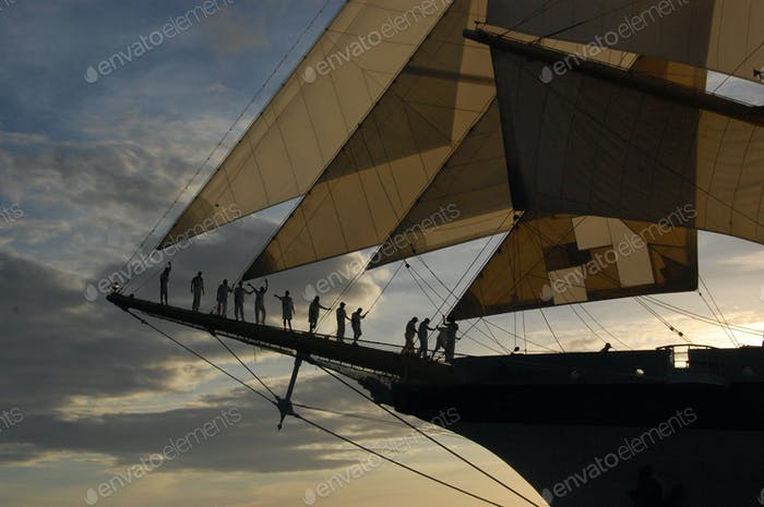 Proud crew on the bow of the Royal Clipper at sunset.