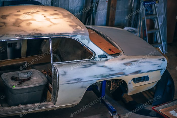 A classic car in a workshop for restoration purposes.