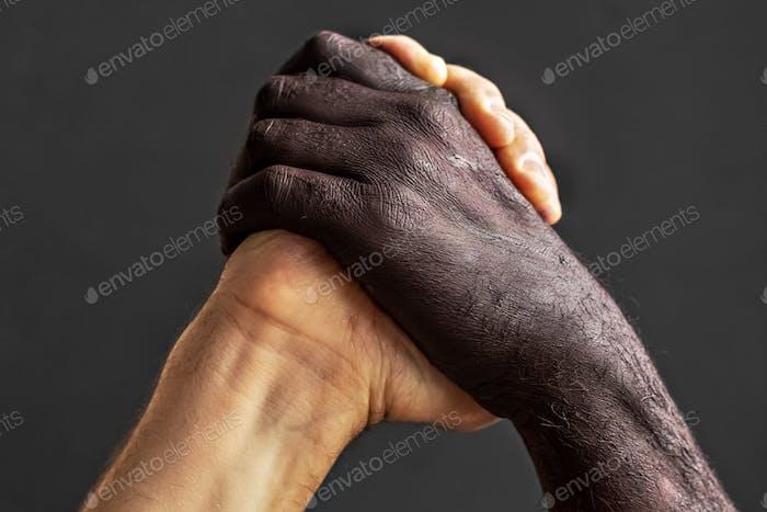 Negro y blanco manos masculinas.El concepto de igualdad y la lucha contra el racismo.