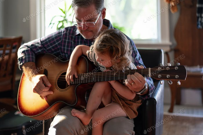 Grandpa playing guitar with his young granddaughter- family, home, lifestyle, music, quality time, s
