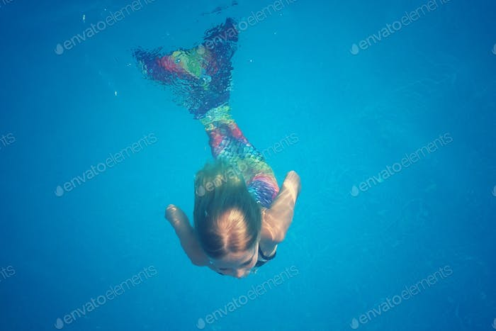 A girl in mermaid costume swimming under water