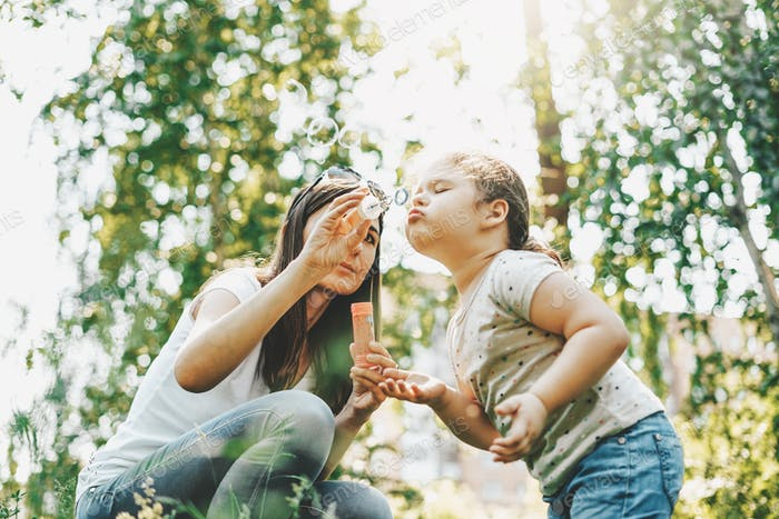 Cute little girl and her mother blow up soap bubbles at park on summer day