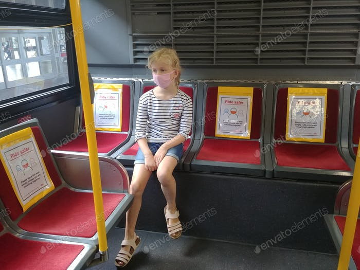 Child girl kid in face mask sitting in public transport bus with covid-19 coronavirus announcement