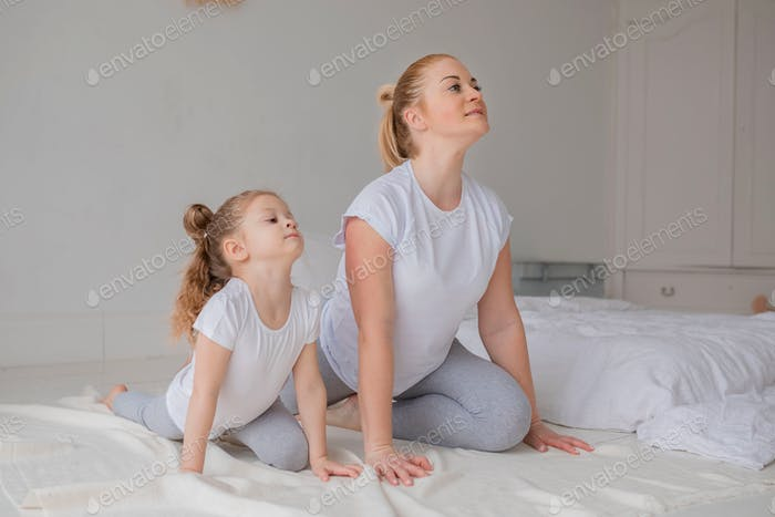 Mommy and daughter doing yoga together.