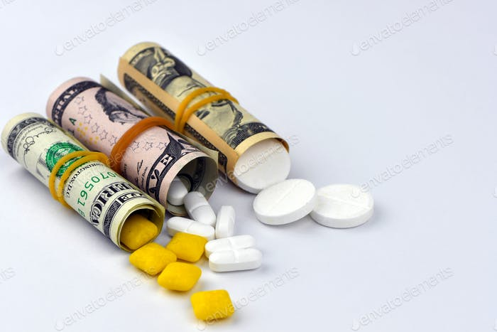 Dollar rolled up with pills flowing out isolated on white background
