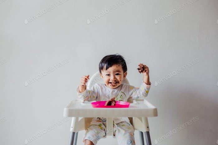 Ein süßer kleiner Junge, der eine Schokolade isst