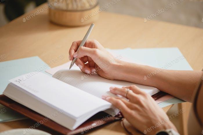 Manos de mujer escribiendo en cuaderno.