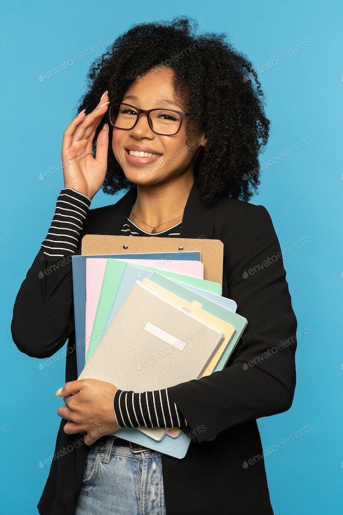 Счастливый студент в блейзере, носить очки, держать тетради, документы и папки, улыбаясь