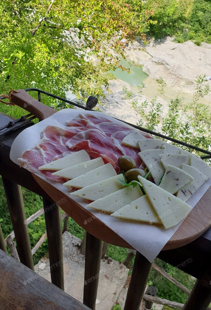 Cold cuts on wooden cutting board. Ham, cheese, olives, local cuisine.