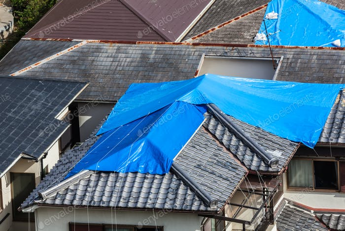 Houses with damaged tiled roof covered by blue sheet after natural disaster