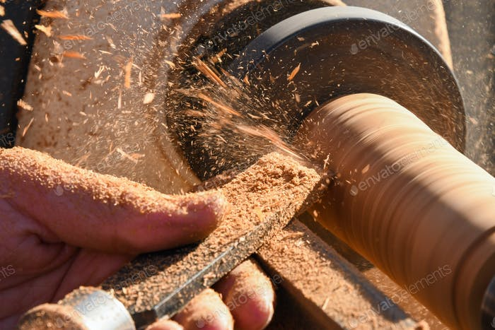 Man using a chisel to carve down a piece of wood on a lathe
