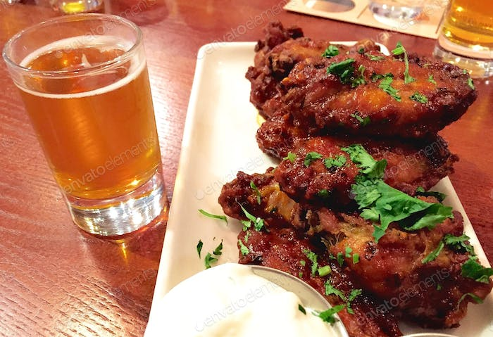 Spicy sriracha barbecue wing appetizer and an ice cold beer on the table at the restaurant