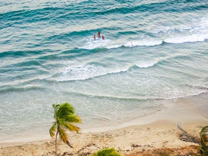 Blick von oben auf eine Meereslandschaft mit Menschen genießen den Strand in Meereswellen und Sand