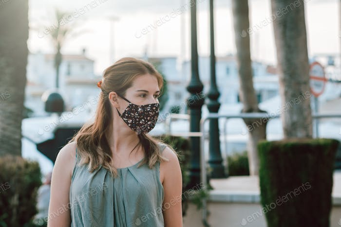 Young woman in fabric face mask outdoors in public place, new normal rules in Spain