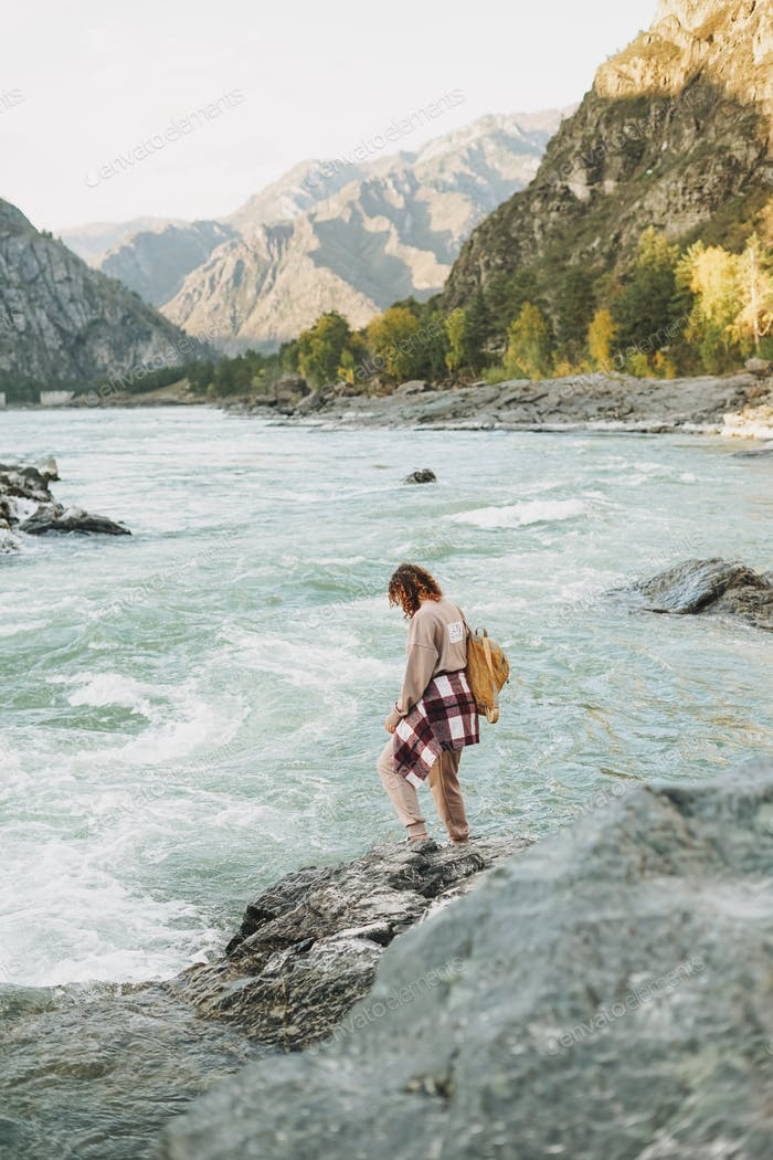 Young woman traveller in casual with backpack on mountain river on sunset