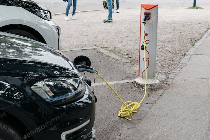 Aufladen eines Elektroautos mit eingestecktem Netzkabel Ladestation