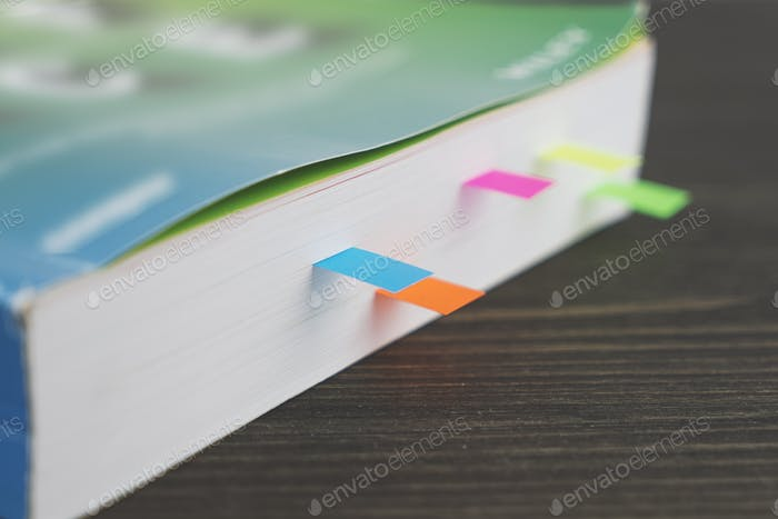 Edge of thick book with colored bookmarks on wooden table, soft focus and Shallow Depth of Field