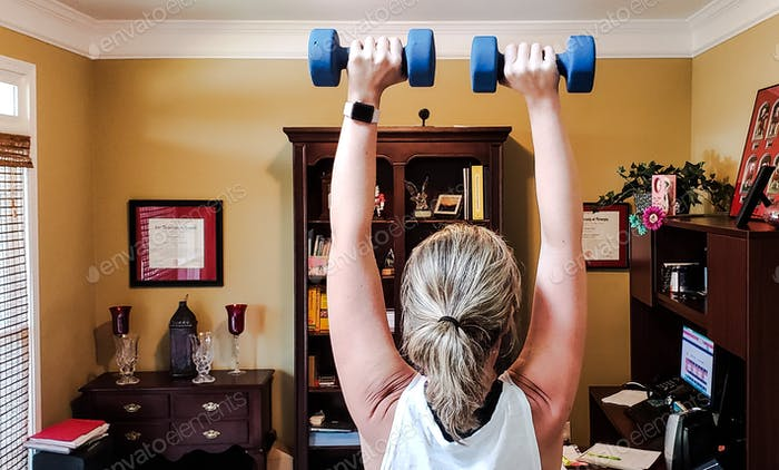 Millenial working woman working out with dumbbells in her home office ...