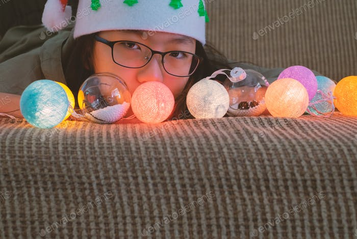 Head shot portrait of a young Asian girl with eyeglasses and Christmas hat on sofa with light bulbs