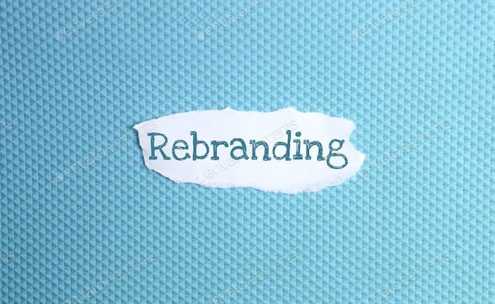 ein zerrissenes Papier mit Rebranding der Inschrift auf blauem Hintergrund