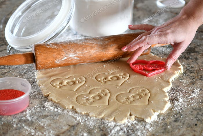 A woman making homemade heart-shaped cutout cookies for my favorite Valentine in the kitchen