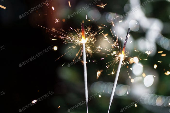 New year's celebration sparklers against Christmas tree background.