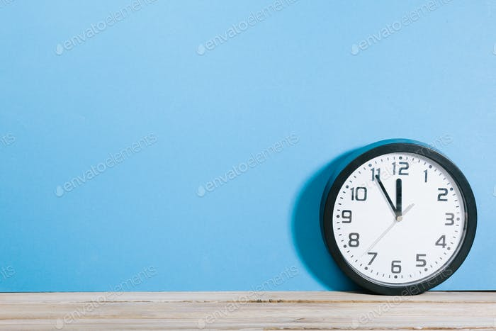 Clock showing five to twelve deadline coming soon on wood office desk with blue wall