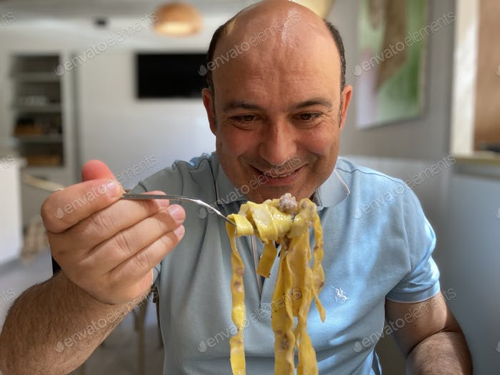 A man eating tagliatelle
