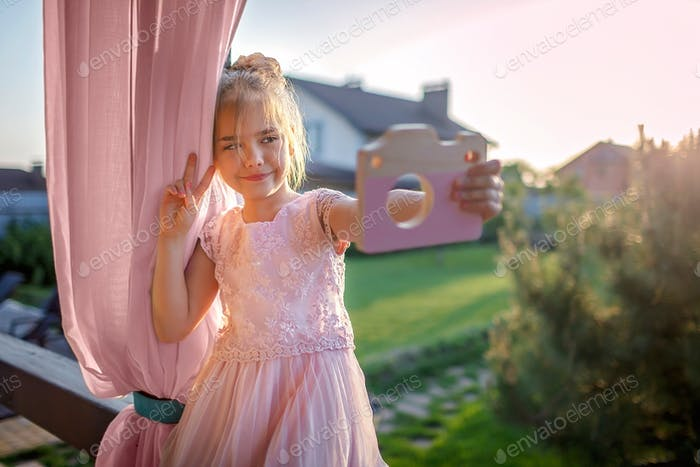 Cute little girl in light pink dress playing with toy wooden camera and imagining like she is doing
