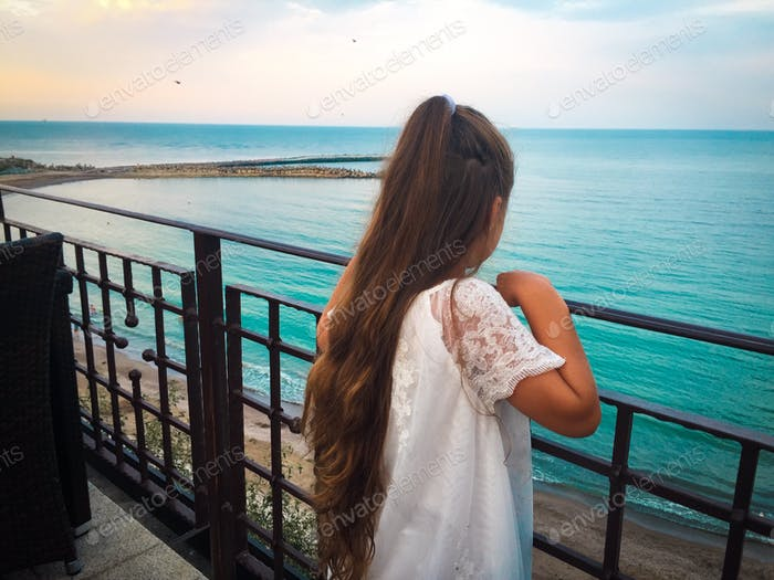 Rear view of little girl with long hair standing on the bridge and looking at the ocean