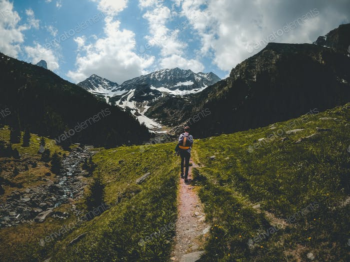 Young man hiking to the mountains. Road trip adventure in Romania's beauty. Fagaras Mountains.