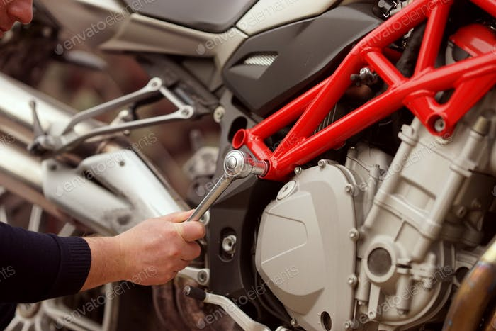 Technician hands of motorbike mechanic repairing a vehicle with a wrench