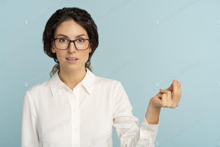 Mujer de negocios haciendo dinero rico gesto con la mano, pidiendo el pago del salario, dinero en efectivo o asignación