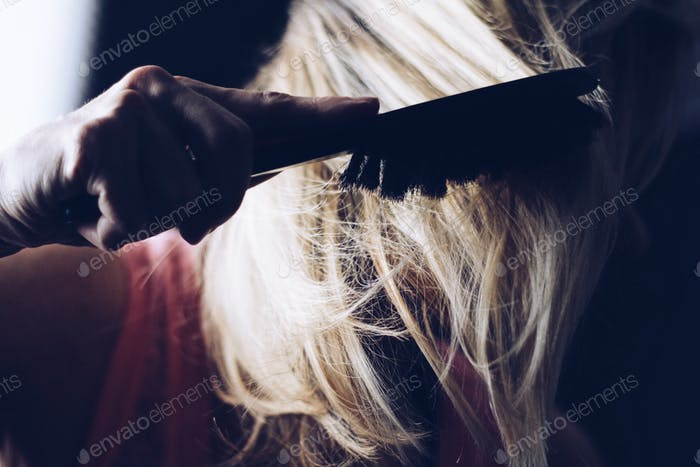 The girl combs hair