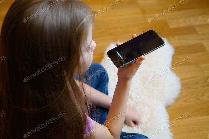 little six year old girl using a smartphone voice recognition online sitting on floor at home