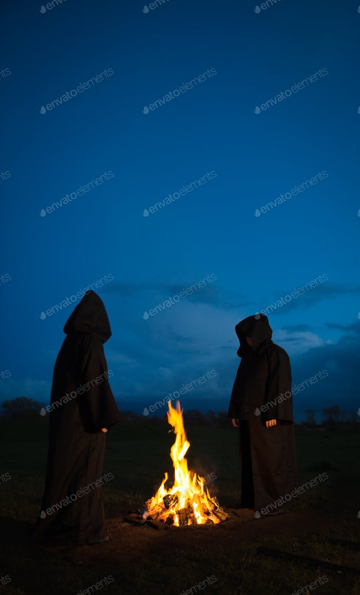 A pair of mysterious hooded figures wearing black cloaks around a bonfire at night in a pagan or