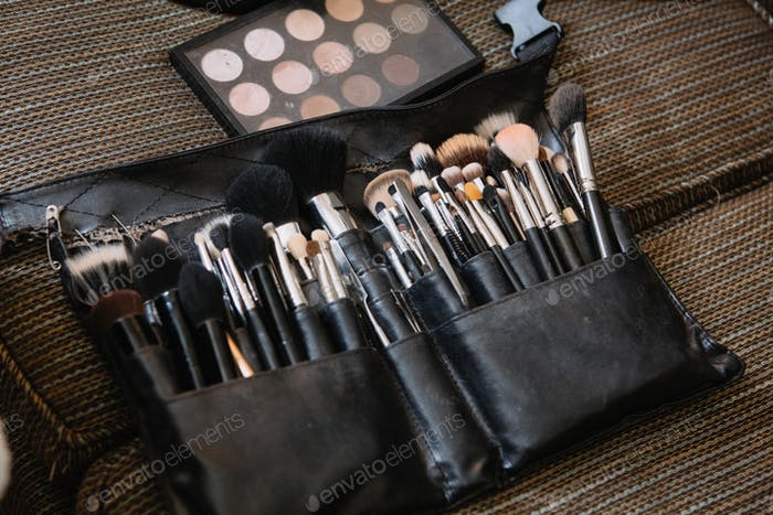 Makeup brushes in a waist pouch.